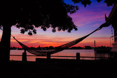 Sunset with hammock in the shadow. Sunset with hammock in silhouette shadow with orange light effect Stock Photography