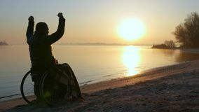 Sunset hands up on wheel chair, lonely disabled on wheelchair, male