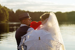 Sunset, happy bride with the groom on the background of water Royalty Free Stock Photo