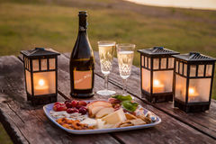 Sunset Happy Hour. Outdoor happy hour at sunset with fruit and cheese platter, `date nite` champagne and candle lanterns Royalty Free Stock Photo