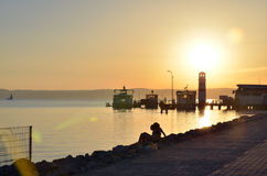 Sunset in the harbor. Lake, boats and a lighthouse. Stock Image