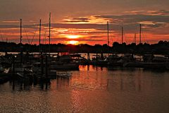 Sunset Harbor. Sunset over an old New England harbor casting a glow of red across the sky and water stock images
