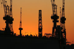 Sunset at the harbor XIV. A picture of a sunset at the harbor in front of some harbor cranes Stock Photo