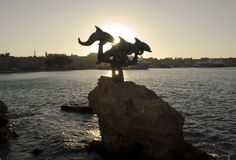 Sunset, harbour of Rhodes, the dolphins statue Royalty Free Stock Images