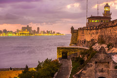 Sunset in Havana with El Morro lighthouse. Beautiful sunset in Havana with El Morro lighthouse illuminated on the foreground Royalty Free Stock Photos