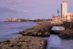 Sunset in Havana with a view of the ocean. The Malecon seawall and El Morro castle in Havana at sunset Royalty Free Stock Photography
