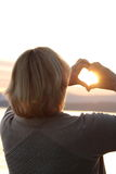 Sunset through heart shaped hands Royalty Free Stock Photography