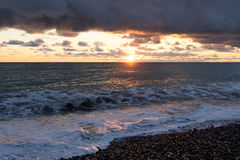 Sunset in heavy dark clouds. Bright sun to heavy dark clouds over the sea Stock Photo