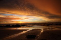 Sunset after heavy rain with arcus shelf storm clouds and stones in the ocean on tropical island Ko Lanta, Thailand stock images