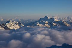 Sunset high in Caucasian mountains. Snowy peaks above the clouds royalty free stock photos