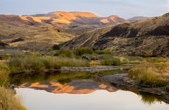 Sunset in the high desert. The setting sun illuminates the mountain top that is reflected in the bend of a slow moving river in the high desert of eastern Oregon stock photography