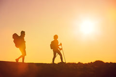 Sunset Hikers. Silhouettes of two hikers with backpacks walking at sunset. Trekking and enjoying the sunset view from mountain top above the clouds Royalty Free Stock Photo