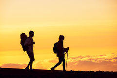 Sunset Hikers. Silhouettes of two hikers with backpacks walking at sunset. Trekking and enjoying the sunset view from mountain top above the clouds Royalty Free Stock Images