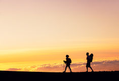 Sunset Hikers. Silhouettes of two hikers with backpacks walking at sunset. Trekking and enjoying the sunset view from mountain top above the clouds Stock Photos