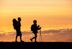 Sunset Hikers. Silhouettes of two hikers with backpacks walking at sunset. Trekking and enjoying the sunset view from mountain top above the clouds Royalty Free Stock Photography