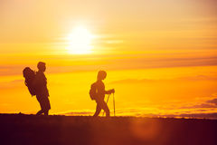 Sunset Hikers. Silhouettes of two hikers with backpacks walking at sunset. Trekking and enjoying the sunset view from mountain top above the clouds Stock Image