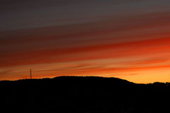 Sunset hill fire color. A late sunset with hills shadow showinf red and orange fire colors in the sky with a bit of clouds Stock Photos
