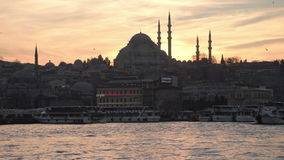 Sunset in the historical part of Istanbul. Istanbul, Turkey - January 11, 2015: Sun sets behind Suleymaniye Mosque and passenger boats wait for their turn at the stock video
