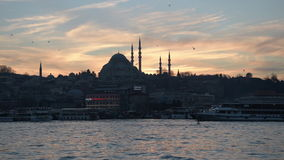 Sunset in the historical part of Istanbul. Istanbul, Turkey - January 11, 2015: Sun sets behind Suleymaniye Mosque and passenger boats wait for their turn at the stock video footage