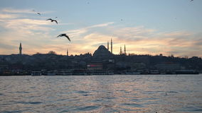 Sunset in the historical part of Istanbul. Istanbul, Turkey - January 11, 2015: Sun sets behind Suleymaniye Mosque and passenger boats wait for their turn at the stock footage