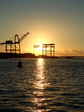 Sunset through Hoisting cranes at container cargo terminals Royalty Free Stock Photos