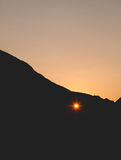 Sunset through the hole in the cliff Royalty Free Stock Photography