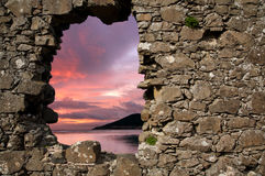Sunset through hole in a wall. A beautiful sunset seen through a hole in a historic  stone wall Royalty Free Stock Image