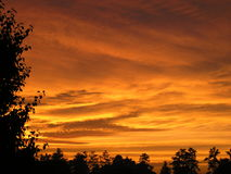 Sunset at home. Fiery orange sunset light up the stormy sky Royalty Free Stock Photography