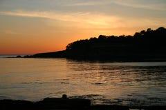 Sunset over forested coastline Stock Photo