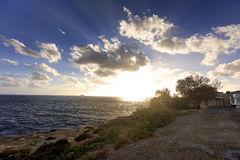 Sunset on the horizon over see and the Blue Grotto area at Malta Royalty Free Stock Photo