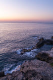 Sunset on horizon with water on rocks Stock Photography