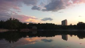 Sunset hour on the lake. Beautiful pink clouds reflect off the surface of the water. People walk around the lake and go to a cafe stock video footage