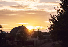 Sunset. House sky sunset village farm fence yellow road trees sun light Stock Images