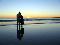 Sunset Hugs Reflected. A romantic view of a couple hugging each other on a beach at the end of a beautiful day Royalty Free Stock Photography