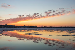 Sunset Through the Ice. A beautiful sunset over downtown Annapolis and the US Naval Academy creates a horizontal symmetry between the sky and the ice-laden Stock Photography