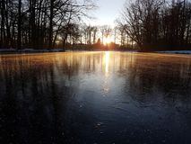 Sunset on ice. Dutch sunset in wintertime. Beautifull mirror effect Royalty Free Stock Photography