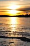 Sunset on ice lake Stock Photography