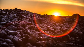 Sunset in Iceland. Sun sets over a rocky and frozen beach in Iceland royalty free stock images