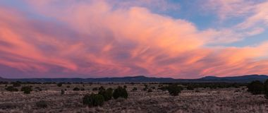 Sunset illuminates swirling dramatic clouds over a desert landscape stock images