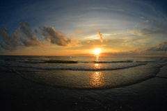 Sunset Indian Rocks Beach. Very wide angle sunset with rolling waves over the sandy beach. Gold sunset with streaking clouds Royalty Free Stock Photos