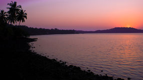 Sunset at the Indian seaside. With silhouettes of coast, palms, trees and hill stock images