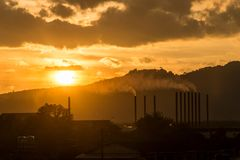 Sunset for industrial buildings with smoking pipes. Sunset for industrial buildings with smoking pipes royalty free stock photography