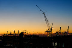 Sunset With Industrial Cranes In Silhouette Royalty Free Stock Photos