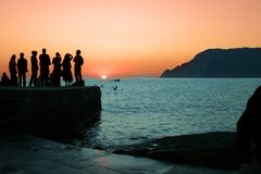 Sunset in Italy. Silhouette of a group of people watching the sunset on the Cinque Terre coast of Itally Stock Image