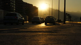 Sunset in Izmir. Along the promenade of the sun. On the horizon, the silhouette of the mountains seen. At the side of the house and the car Royalty Free Stock Photography