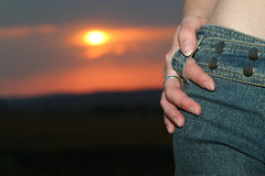 Sunset jeans. Girl in blue jeans at sunset royalty free stock photography