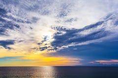 Sunset on Jimbaran, South Kuta, Bali, Indonesia. Beautiful blue sky and orange sun behind the clouds over the sea stock image