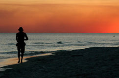 Sunset Jog. Man jogging down the beach with sunset and ocean Stock Photography