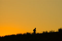 Sunset jogging. Silhouette of lonely jogger at sunset Stock Photo