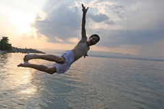 Sunset jump. Boy joyfully jumping in the lake at sunset stock photography